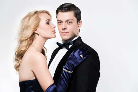 dinner jacket: Romantic new years eve fashion couple. Woman kissing man. Wearing black dinner jacket and blue dress. Isolated against white.