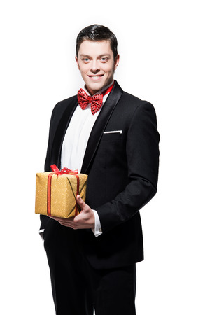 dinner jacket: New years eve fashion man wearing black dinner jacket with big red bow tie. Holding gold present. Isolated against white.