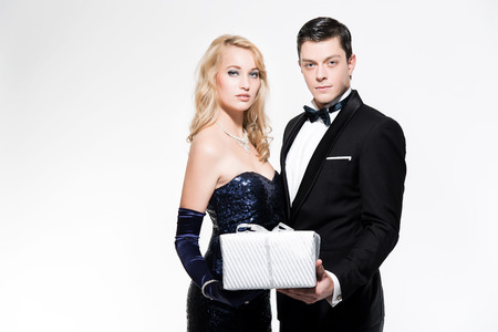 dinner jacket: Romantic new years eve fashion couple wearing black dinner jacket and dark blue dress. Holding silver present. Isolated against white. Stock Photo