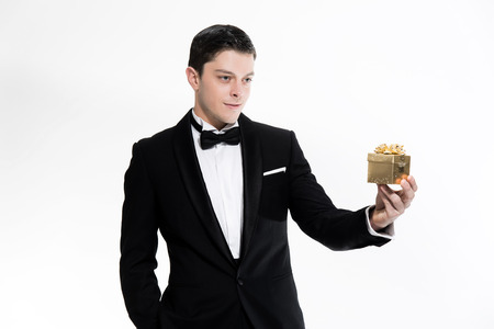 dinner jacket: New years eve fashion man wearing black dinner jacket. Holding golden present. Isolated against white.