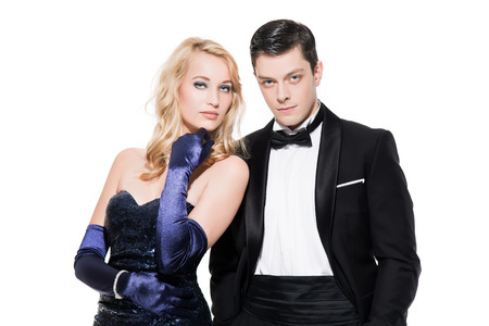 dinner jacket: Romantic new years eve fashion couple wearing black dinner jacket and dark blue dress. Isolated against white.