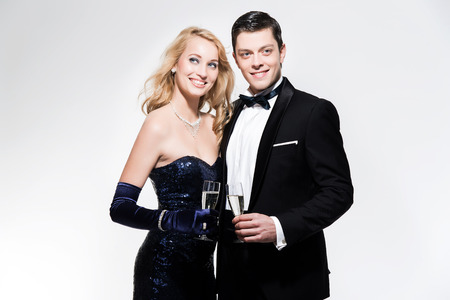 Romantic new year's eve fashion couple toasting with champagne. Wearing black dinner jacket and blue dress. Isolated against white.