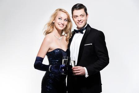 Romantisches Silvester Mode Paar mit Champagner rösten. Mit schwarzen Smoking und blauen Kleid. Einzeln gegen weißen. Standard-Bild - 34628599