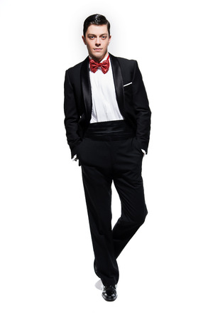 dinner jacket: New years eve fashion man wearing black dinner jacket with big red bow tie. Isolated against white.