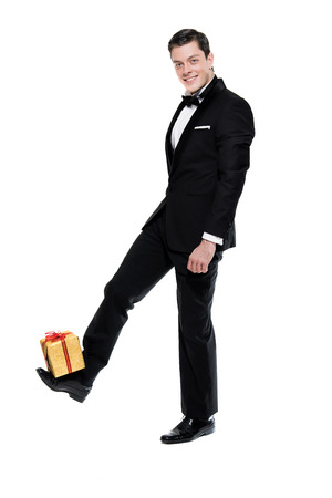 dinner jacket: New years eve fashion man wearing black dinner jacket. Balancing golden present on shoe. Isolated against white. Stock Photo