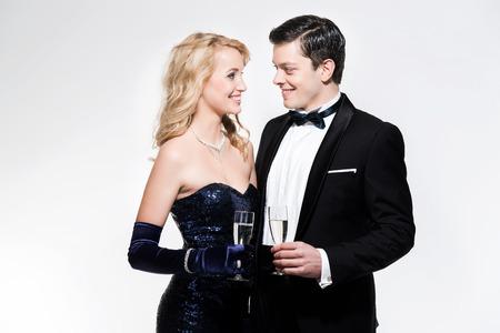 lazo negro: Pareja de moda romántica víspera de año nuevo brindando con champán. El uso de esmoquin negro y vestido azul. Aislado contra blanco.