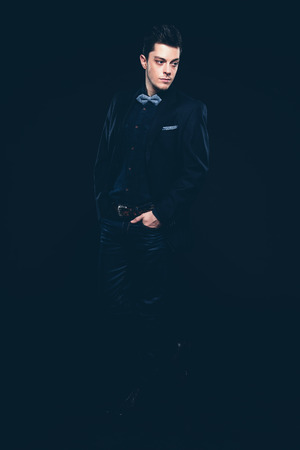 hair tie: Retro fashion man with blue shirt, jacket, jeans and bow tie. Short dark hair. Studio shot against black.