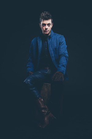 short gloves: Winter jeans fashion man with short dark hair. Wearing blue jeans, jacket, brown leather boots and gloves. Sitting on old wooden box. Studio shot against black.