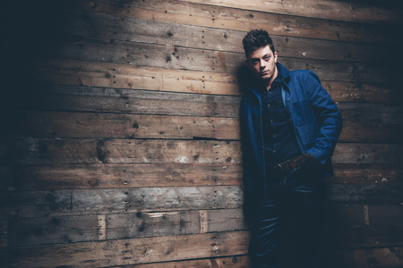 short gloves: Winter jeans fashion man with short dark hair. Wearing blue jeans, jacket and brown leather gloves. Leaning against old wooden wall.