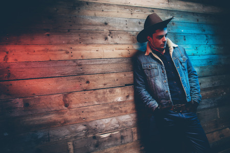 Winter cowboy jeans fashion man. Wearing brown hat, jeans jacket and trousers. Leaning against old wooden wall. Stok Fotoğraf