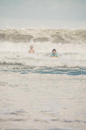 bodyboard: Father on bodyboard of his son in waves having fun. Stock Photo