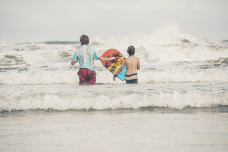 bodyboard: Father and son walking with bodyboard into the waves of ocean.