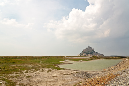 Coastal view of the island of Mont St Michel in Normandy France with its fortified monastery, an important pilgrimage and tourist destination Banco de Imagens - 36189924
