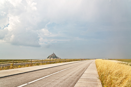 Deserted road leading to the tidal island of Mont St Michel off the coast of Normandy France with its fortified abbey and monastery and a popular tourist destination