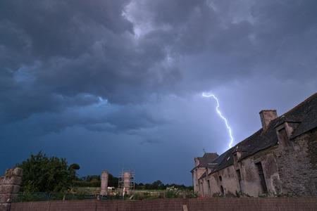 farmyard: Dramatic thunderstorm with lightning strikes from threatening gloomy dark clouds over a rural stone farmhouse and farmyard