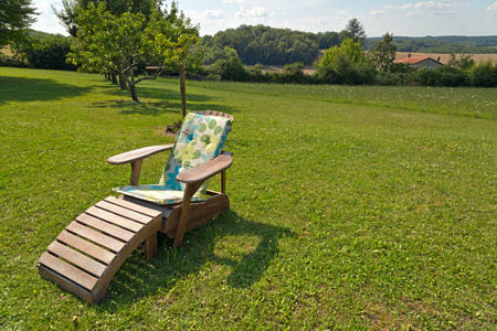 recliner: Comfortable wooden recliner chair on a lush green lawn in a rural garden in summer sunshine to relax and unwind