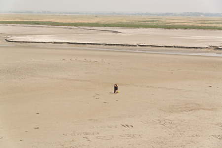 vast: Couple Standing Together on Sand on Vast Beach at Normandy, France Stock Photo