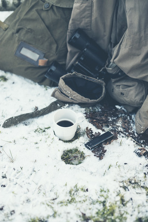 belongings: Close up Cup of Coffee and Belongings of a Traveler on the Ground with Snow