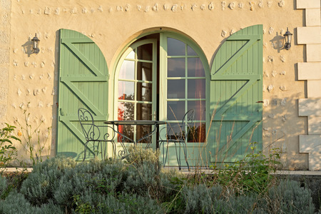 ajar: Arched glass front door with green shutters standing slightly ajar in evening sunshine in a beige textured exterior wall of a house