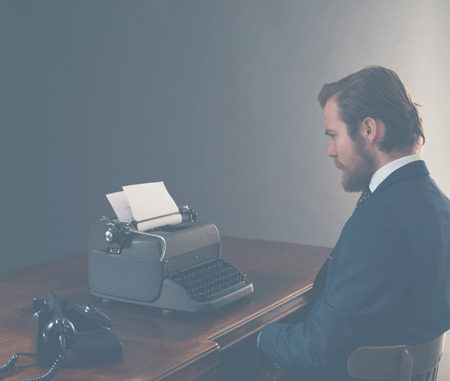 side effect: Vintage businessman sitting at his desk with an old-fashioned rotary telephone and manual typewriter, side view with aged effect