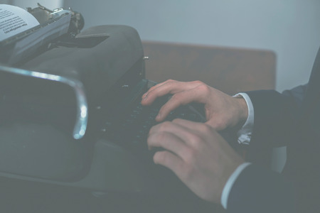 olden day: Faded image of a businessman or journalist using a vintage manual typewriter, close up view of his hands