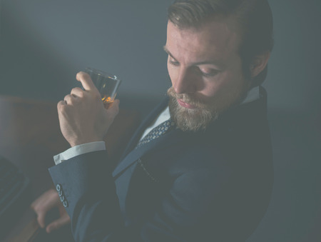 whiskey: Close up of a stylish handsome bearded man enjoying a brandy or whiskey while looking thoughtfully downwards, aged effect Stock Photo