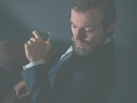 hombre barba: Primer plano de un hombre con barba estilo guapo disfrutando de una copa de coñac o whisky mientras mira cuidadosamente hacia abajo, efecto envejecido
