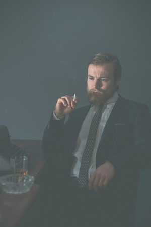 olden day: Vintage businessman sitting in his office at his desk smoking a cigarette and staring thoughtfully at the floor