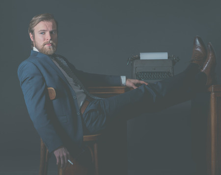 olden day: Successful vintage businessman relaxing in the office with his feet on the desk alongside an old manual typewriter looking thoughtfully to the side with a pensive expression