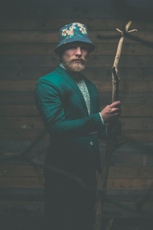 Portrait of a Serious Middle Age Man with Goatee in Green Formal Wear with hat Holding a Dry Tree Branch in front of a Wooden Wall While Looking at the Camera