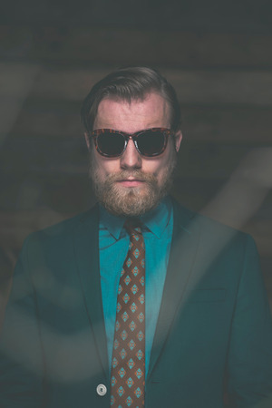 facing to camera: Close up Portrait of an Adult Man with Goatee Beard Wearing Formal Fashion with Sunglasses Facing at the Camera. Stock Photo
