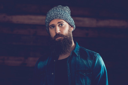 bonnet up: Close up Handsome Young Man with Long Beard Wearing Trendy Denim Jacket and Gray Knitted Bonnet Outfit. Stock Photo