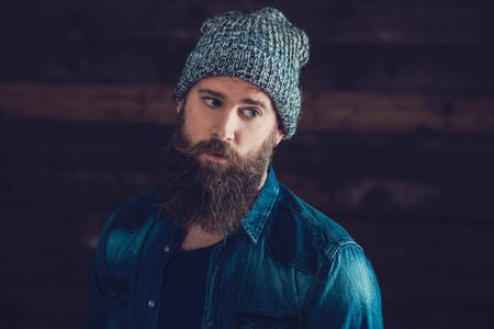 bonnet up: Close up Stylish Young Guy with Long Goatee, Wearing Casual Denim Jacket and Bonnet Outfit. Stock Photo