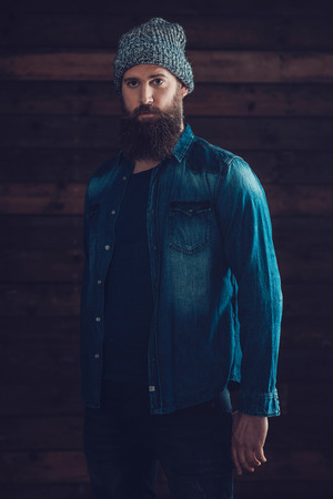 long beard: Serious Young Man with Long Beard Wearing Casual Denim Jacket and Knitted Hat Outfit, Standing In Front a Wooden Wall Background.