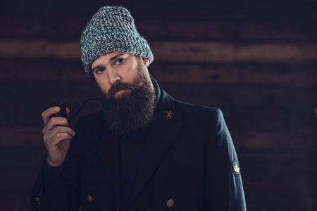 expressionless: Close up Gorgeous Man with Long Beard, Wearing Black Coat and Gray Bonnet, Holding a Smoking Pipe While looking at the Camera.