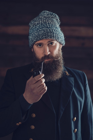 bonnet up: Close up Stylish Handsome Man with Long Beard, Wearing Black Coat and Bonnet, Smoking Using a Pipe While Looking at the Camera