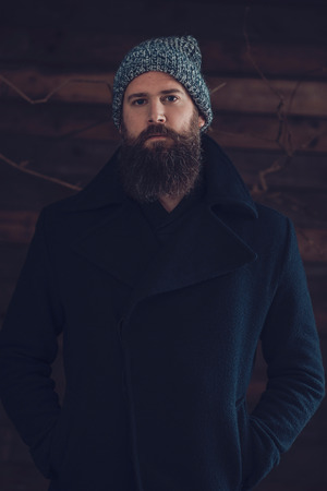 bonnet up: Close up Serious Man with Long Goatee Wearing Plain Black Winter Coat and Gray Bonnet While looking at the Camera. Stock Photo