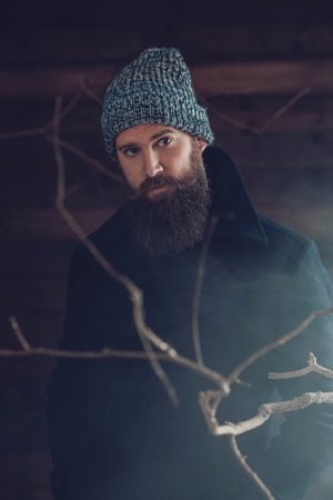 observant: Close up Handsome Young Man with Long Goatee, Wearing Winter Fashion Behind Dry Twigs and Smoke, Looking at the Camera.