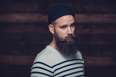 bonnet up: Close up Good Looking Man With Long Goatee Wearing Stripe Shirt and Bonnet on a Wooden Wall Background. Stock Photo