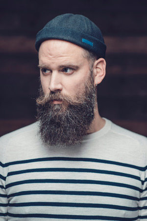 bonnet up: Close up Serious Handsome Guy with Long Beard, Wearing Casual Stripe Shirt and Bonnet, Looking to the Left of the Frame. Stock Photo