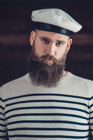 goatee: Close Up Portrait of a Gorgeous Man with Long Goatee Wearing Black and White Stripe Shirt and Sailor Hat, Looking at the Camera.