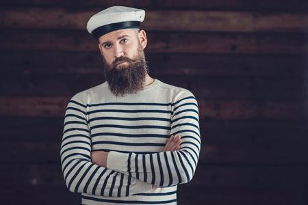 marinero: La mitad Shot cuerpo de un hombre serio con la barba larga Wearing moda Negro y blanco de la raya Camisa y Sombrero de marinero Vestimenta, cruzándose de brazos mientras mira a la cámara.