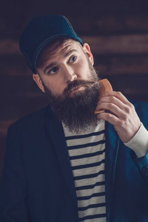 Close up Portrait of a Handsome Man in Trendy Clothing with Cap Combing his Beard Seriously. Stock Photo
