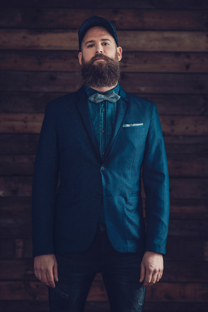 expressionless: Portrait of a Handsome Goatee Man, Wearing Dark Blue Formal Wear with a Cap, Looking at the Camera on a Wooden Wall. Stock Photo