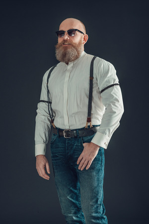 goatee: Portrait of an Adult Bald Goatee Man Wearing White Long Sleeves Shirt and Jeans with Suspenders on a Gray Background.