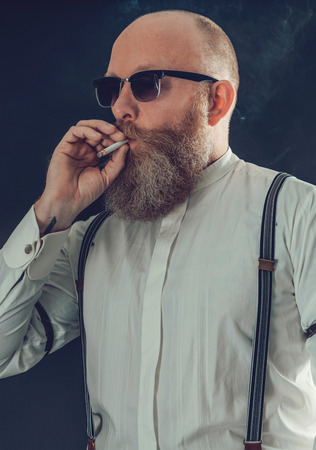 eye wear: Close up Middle Age Bald Goatee Man, in White Long Sleeves Shirt with Suspenders and Eye Wear, Smoking a Cigarette on a Gray Background.