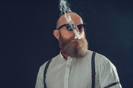 Close up Serious Bald Goatee Male Smoker in White Shirt with Sunglasses Isolated on a Gray Background Stock Photo
