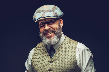 dapper: Handsome bearded man with a lovely smile wearing a cloth cap and waistcoat standing looking at the camera, head and shoulders on black