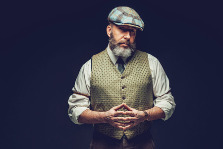 introspective: Half Body Shot of a Middle Age Man in a Trendy Green Outfit with Ivy Cap, Posing on Black Background with Hands In front his Belly While Looking at the Camera Seriously.