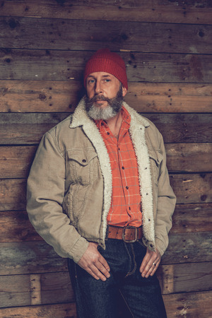 speculate: Close up Portrait of a Senior Goatee Man in Trendy Clothing with Red Bonnet Leaning on the Wooden Wall While Looking at the Camera. Stock Photo